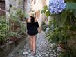 Spacer kobiety w kapeluszu romantyczną włoską uliczką. Sermoneta, Italia