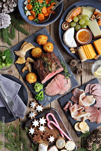 Christmas dinner table with roast beef, appetizers platter and traditional cookies. Christmass celebration, festive family dinner.  Overhead view. - 297386428