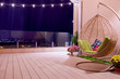 Leinwanddruck Bild - rooftop patio area with hanging swing chair and string lights at night