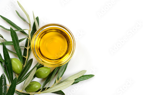 Olive oil. Greek olive oil in glass transparent bowl with branches with leaves and olives, with copy space. Close-up, Isolated on white background.