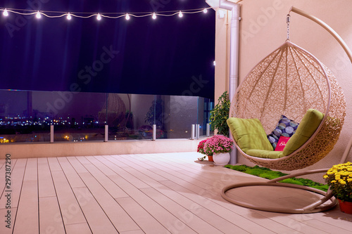 rooftop patio area with hanging swing chair and string lights at night Fototapet