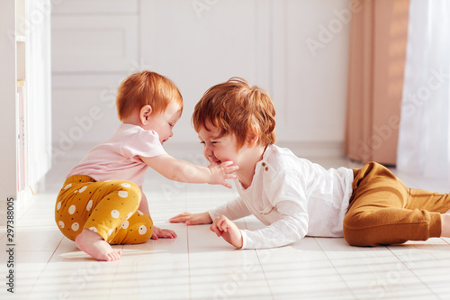 Photographie cute happy redhead siblings, brother and sister having fun together, playing at