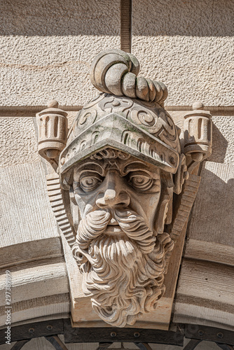 Photo  Very old statute of scary and heavy armed gatekeeper, medieval warrior with weap