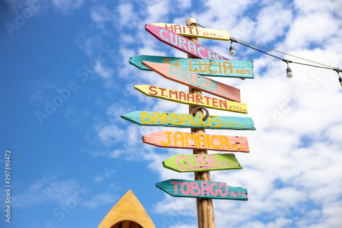 Fotografía  signpost showing the way to exotic destinations on background of blue sky