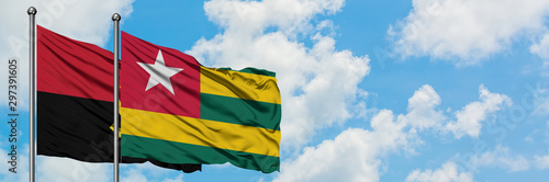 Fotografía  Angola and Togo flag waving in the wind against white cloudy blue sky together