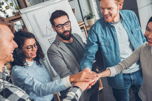 Fotografía  Startupers working at office together standing holding hands motivating top view