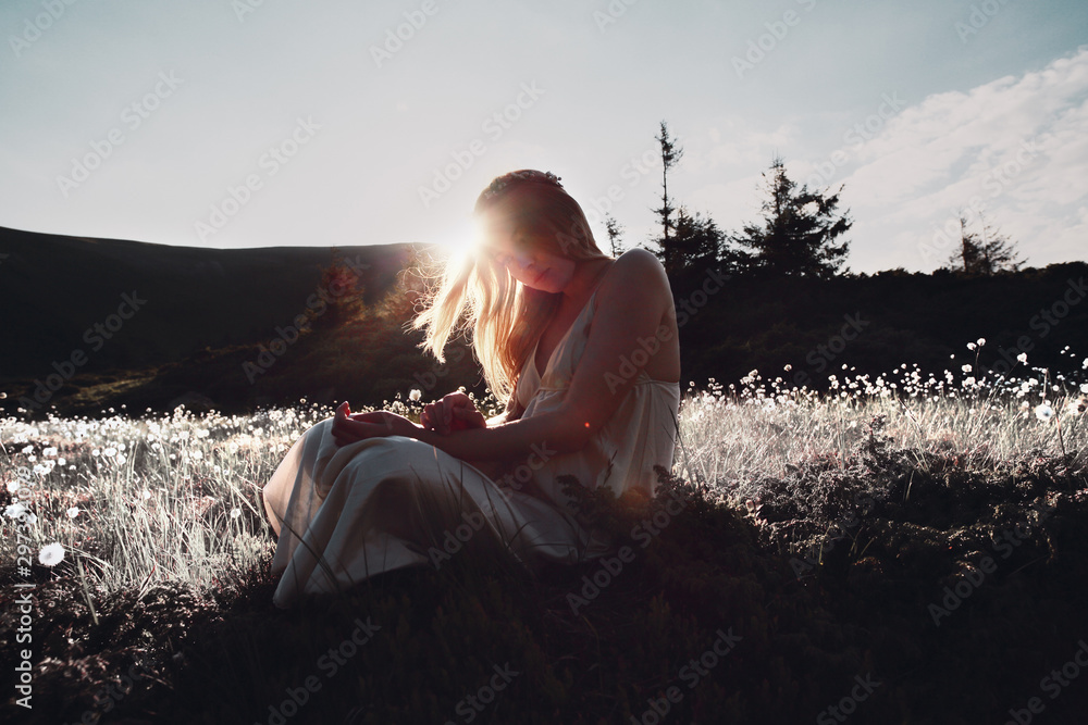 Fototapety, obrazy: Young caucasian woman in dress resting on a mountain peak at sunset.