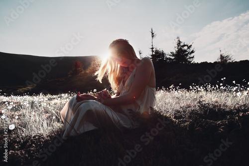 Foto auf Gartenposter Schokobraun Young caucasian woman in dress resting on a mountain peak at sunset.