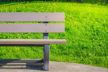 Empty Brown Bench On Green Grass And Yellow Flowers With Bright Sun Light In The City Park During Summer Sunny Day