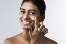 Beautiful Indian Woman Applying Moisturizing Cream On Her Face