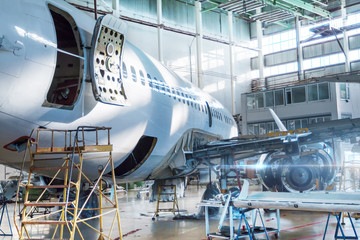 Passenger jet plane under maintenance in the hangar. Checking mechanical systems for flight operations. Close-up view the back of the aircraft with the door open