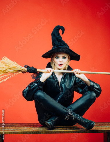 Emotional young women in halloween costumes on party over red background with pumpkin. Witch holding broom or broomstick.