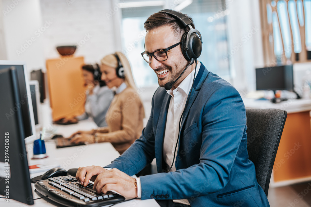 Fototapety, obrazy: Handsome male customer service agent working in call center office as a telemarketer.