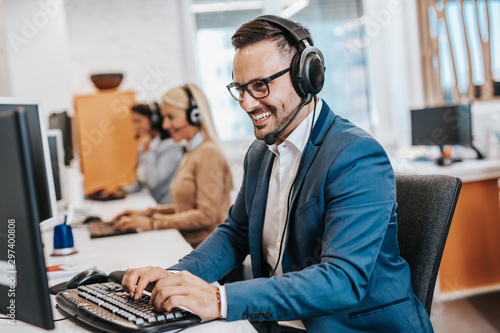 Handsome male customer service agent working in call center office as a telemarketer Fototapet