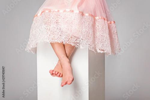 Pinturas sobre lienzo  Little cute girl in pink dress is sitting barefeet on white cube
