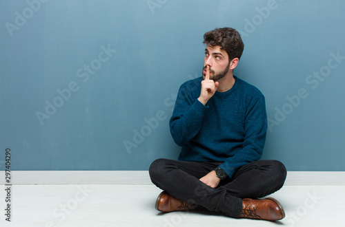 Valokuvatapetti young handsome man sitting on floor asking for silence and quiet, gesturing with