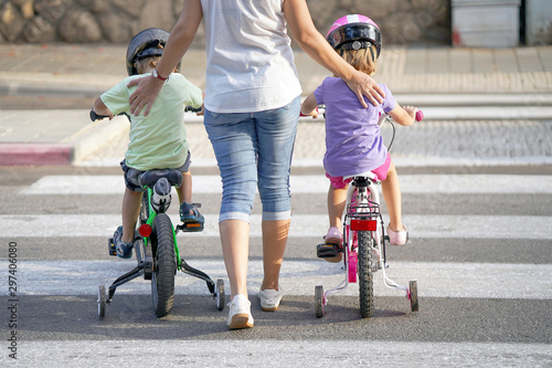 Mother goes pedestrian crossing with children on bicycles Fototapet