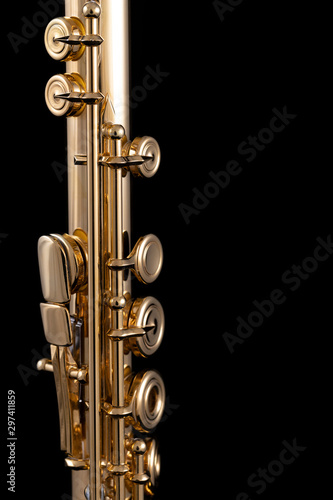 Photo A part of a gold plated flute on a black background