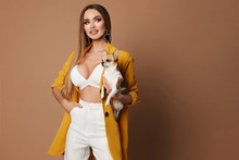 Sexy Girl With A Perfect Body Posing With Chihuahua, Isolate. Trendy Model With Big Bust Wearing Unbuttoned Yellow Jacket, White Top And Jeans.