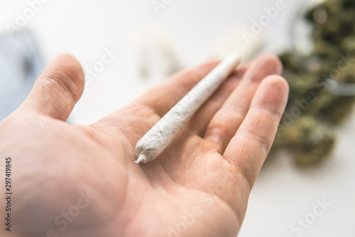 Valokuva  joint with marijuana weed on hand , close up, Cannabis buds on white table backg