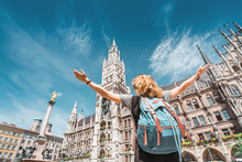 A Girl Tourist Traveler Enjoys A Grand View Of The Gothic Building Of The Old Town Hall In Munich. Sightseeing And Exploration Of Germany Concept