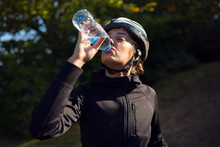 Female Cyclist Drinking Water From Bottle