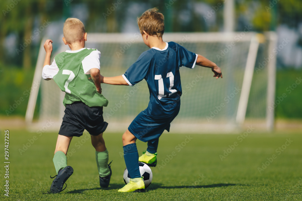Fototapety, obrazy: Training and football match between youth soccer teams. Young boys playing soccer game. Hard competition between players running and kicking soccer ball. Final game of football tournament for kids.