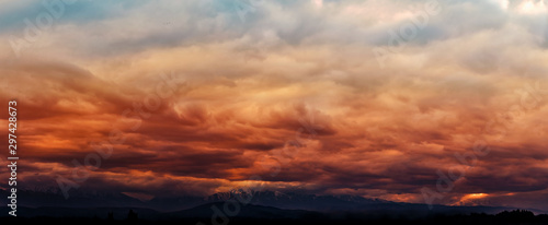 Dramatic light through the clouds against the backdrop of an exciting, vibrant stormy sky at sunset, dawn in the mountains Canvas-taulu