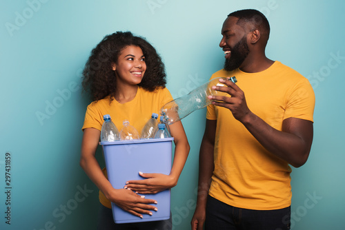 Fotografía  Happy couple hold a plastic container with bottles over a light blue color