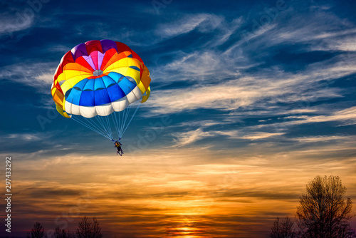 Fototapeta A man is gliding with a parachute on the background of sunset.