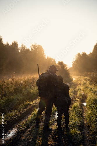 Tableau sur Toile Rifle Hunter and His Son Silhouetted in Beautiful Sunset