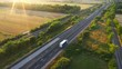 Aerial Drone Footage: Long Haul Semi Trucks Driving on the Busy Highway in the Rural Region of Italy. Agricultural Crop Fields and Hills in the Background