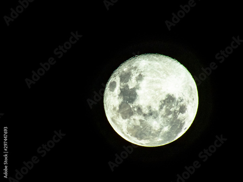 Moon in the middle of its way on the clear sky. Wallpaper Mural