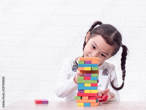 Fotografia Asian little cute girl playing wooden blocks on wooden table and white wall background