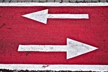 Left And Right White Dirrection Arrows On Neon Red Surface Of A City Biking Lane.