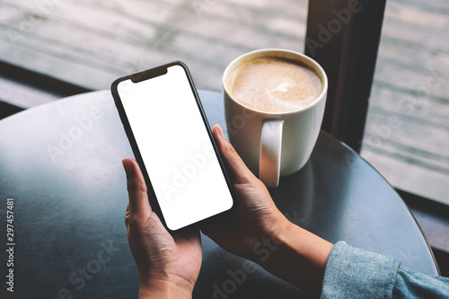 Mockup image of a woman holding black mobile phone with blank screen with coffee Fototapet
