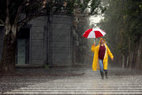 Happy young man with colorful umbrella outdoors on rainy day