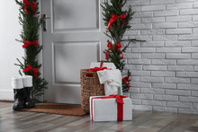 Stylish Hallway Interior With Decorated Door And Christmas Gifts, Space For Text