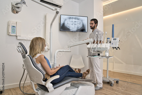 Fototapeta Black hair and beard dentist shows the client the x-ray of his mouth. Western client with blond hair was tumbling in the clinic chair. Modern dental clinic xray concept. obraz na płótnie