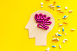 Treat brain diseases. Head with plastiline meanders and pills on yellow background top view space for text
