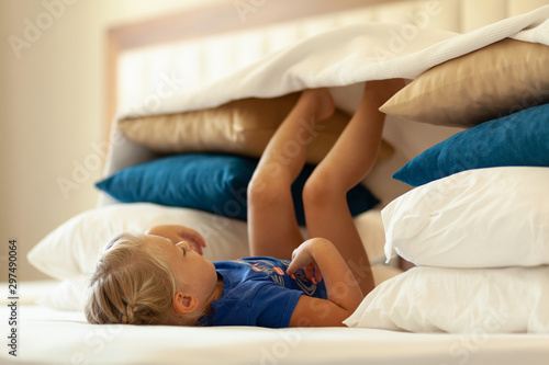 Little cute girl built impromptu fort (castle, house) out of pillows and blankets on bed Fototapeta