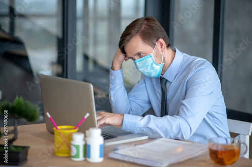Foto auf Gartenposter Tee Office worker wearing protective mask after catching cold