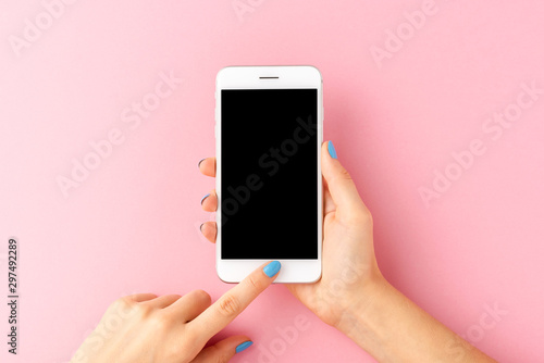 Fotografia  Overhead shot of woman's hands holding mobile phone with empty screen on pink background