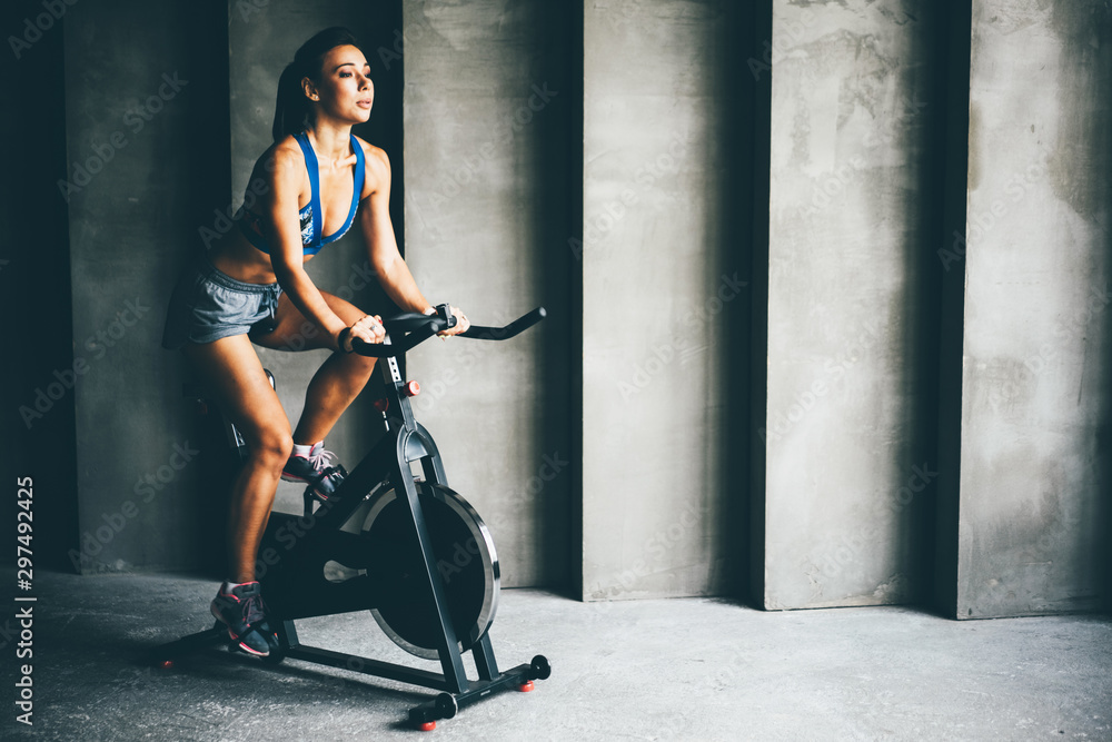 Fototapety, obrazy: Attractive young woman at the gym riding on spinning bike. Healthy Lifestyle and Sport Concepts.