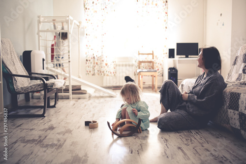 Fotografía  happy mom with two children on the floor in room