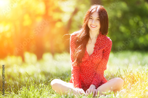 Foto auf Leinwand Gelb Schwefelsäure Young cute woman in red dress relaxing in the park. Beauty nature scene with colorful background, trees at summer season. Outdoor lifestyle. Happy smiling woman sitting on green grass