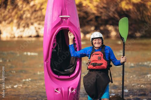 Fototapeta Senior man preparing for kayak tour on a mountain river.