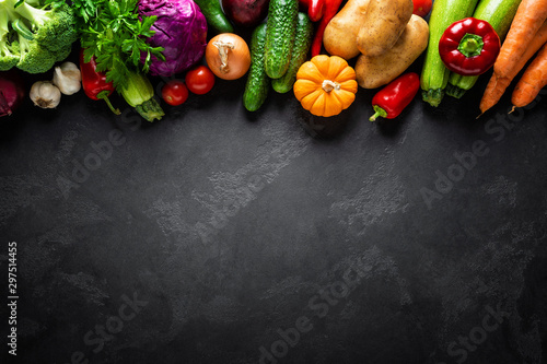 Fotografía  Culinary background with fresh raw vegetables on a black kitchen table, healthy