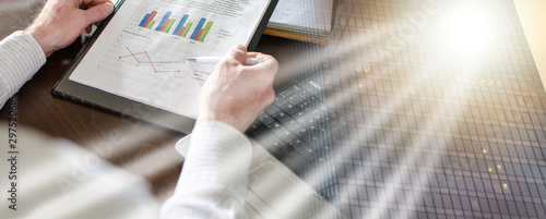 Photo Businessman analysing economic graphs; multiple exposure