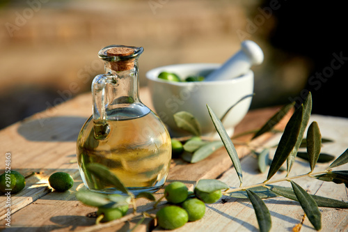 Fototapeta olive oil and green olive on the wooden background obraz